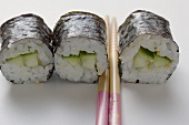 Three maki sushi with cucumber and chopsticks