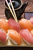 Nigiri sushi, chopsticks and pot