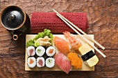 Assorted sushi on sushi board, hand towel and pot beside it