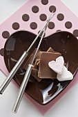 Small bowl with chocolate pieces, marshmallow & fondue forks