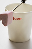 Beaker with the word 'love' and fondue fork with marshmallow