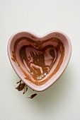 Heart-shaped bowl with remains of chocolate sauce