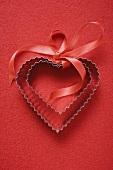 Heart-shaped biscuit cutters with red gift ribbon