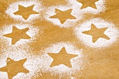 Star shapes outlined in icing sugar on wooden background