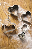 Heart-shaped biscuit cutters on floured board
