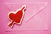 Pink envelope and red heart-shaped biscuit with arrow