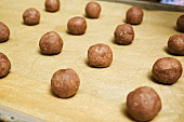Small balls of hazelnut dough on a baking tray