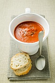 Creamed pepper soup in soup cup, spoon and baguette slices