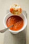 Red pepper cream soup in soup cup, spoon & baguette slices