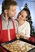 Young couple with freshly baked Christmas biscuits