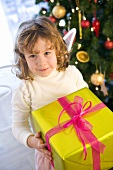 Girl dressed as angel with Christmas gift