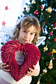 Girl dressed as angel in front of Christmas tree