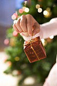 Hand holding small parcel in front of Christmas tree