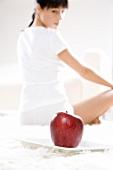 Ein roter Apfel, dahinter junge Frau