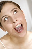 Young woman with an ice cube in her mouth