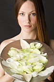 Red-haired woman with a bowl of white rose petals