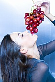Woman holding red grapes over her mouth