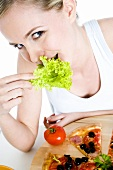 Junge Frau isst Salatblatt