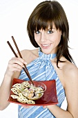 Young woman holding Asian noodle dish and chopsticks