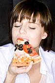 Young woman eating a slice of pizza