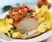 Roast loin of pork with apple wedges and bacon