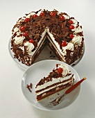 Black Forest gateau with pieces taken & a piece on a plate