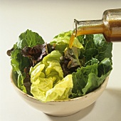 Pouring dressing over mixed lettuce leaves