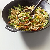 Strips of chicken breast and vegetables in wok