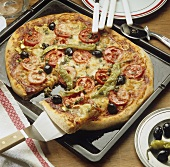 Wholemeal pizza topped with tomatoes, olives and chillies