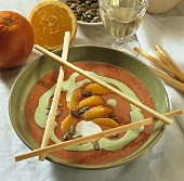 Creamed tomato soup with orange segments, pumpkin seeds & grissini