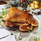 Roast goose with figs on festive table
