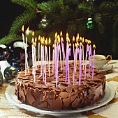 Chocolate cake with many burning candles