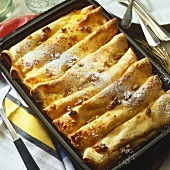 Crêpes with vanilla cream and nuts in baking dish