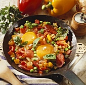 Fried eggs, vegetables and sausage in frying pan
