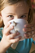 Young girl drinking a cup of hot chocolate