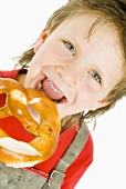 Boy biting into a pretzel