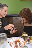 Man giving woman a ring in a restaurant
