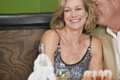 Mature man embracing woman in restaurant