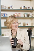 Mature woman at laptop with a cup of coffee