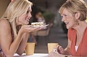 Two women in a café with a piece of tiramisu