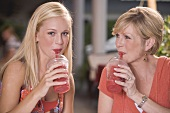 Young woman & mature woman drinking frozen strawberry smoothies