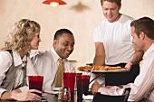 Mann serviert Gästen Pizza