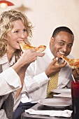Man and woman eating pizza