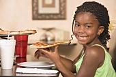 Girl in restaurant eating a slice of pizza