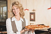Blond woman holding a pizza