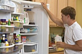 Man in T-shirt examining the contents of his refrigerator