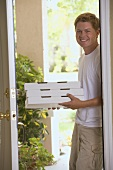 Man standing at house door with pizza boxes