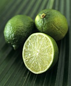 Limes, two whole and one half, on a palm leaf