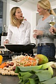 Women with glasses of wine chatting while preparing food