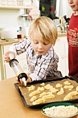 Boy piping biscuit dough onto baking tray with biscuit syringe